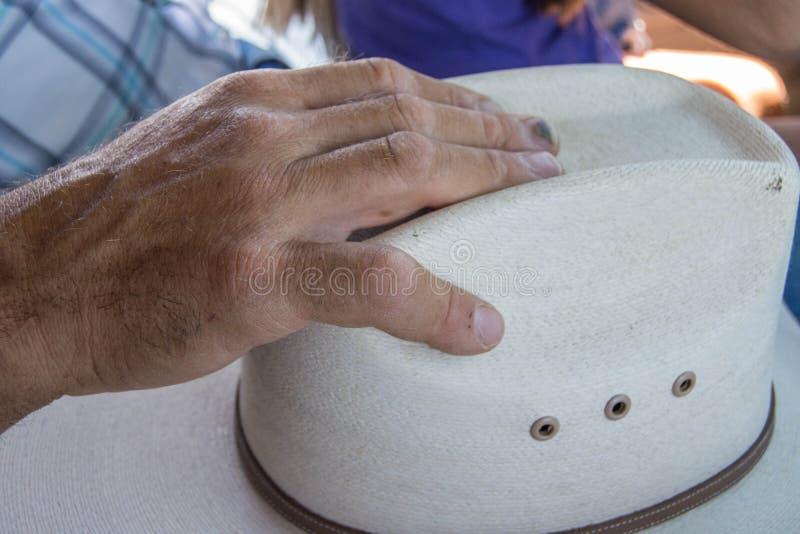 Il funzionamento equipaggia le mani sul cappello da cowboy immagini stock libere da diritti