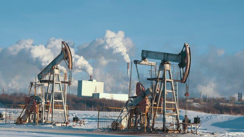 Il funzionamento pompa per produzione del petrolio greggio contro lo sfondo della centrale petrolchimica fotografia stock libera da diritti