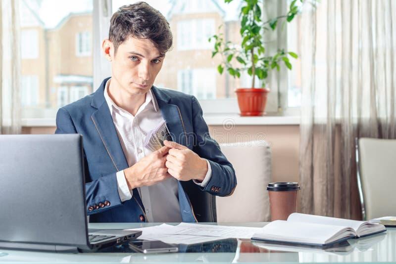 Il funzionario dell'uomo d'affari che si siede nell'ufficio nasconde un dono inosservato in sua tasca Corruzione e corruzione immagine stock libera da diritti