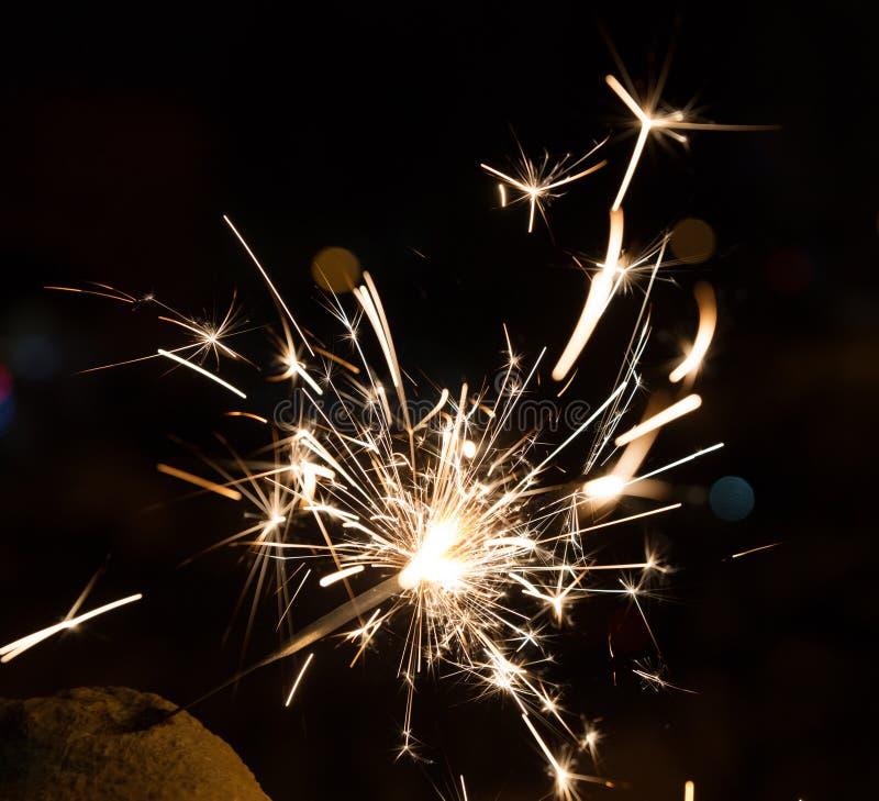 Il fuoco del Bengala scintilla contro lo sfondo delle luci della città, bokeh vago fotografia stock