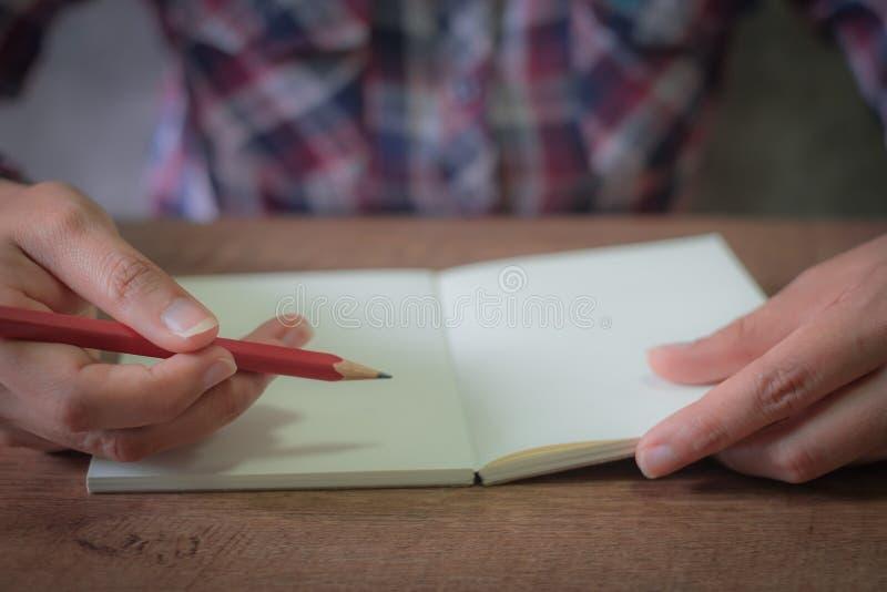 Il fuoco delle mani femminili che tengono la matita rossa per scrive il libretto vuoto fotografia stock