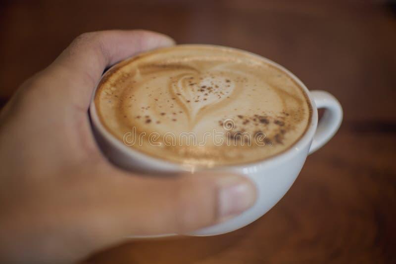 Il fuoco molle di una tazza di caffè caldo in maschio asiatico passa la tenuta dentro fotografia stock libera da diritti