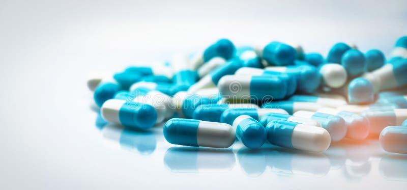 Il fuoco selettivo sulla pillola di bianco e blu delle capsule si è sparso su fondo bianco con ombra r antibiotici fotografie stock libere da diritti