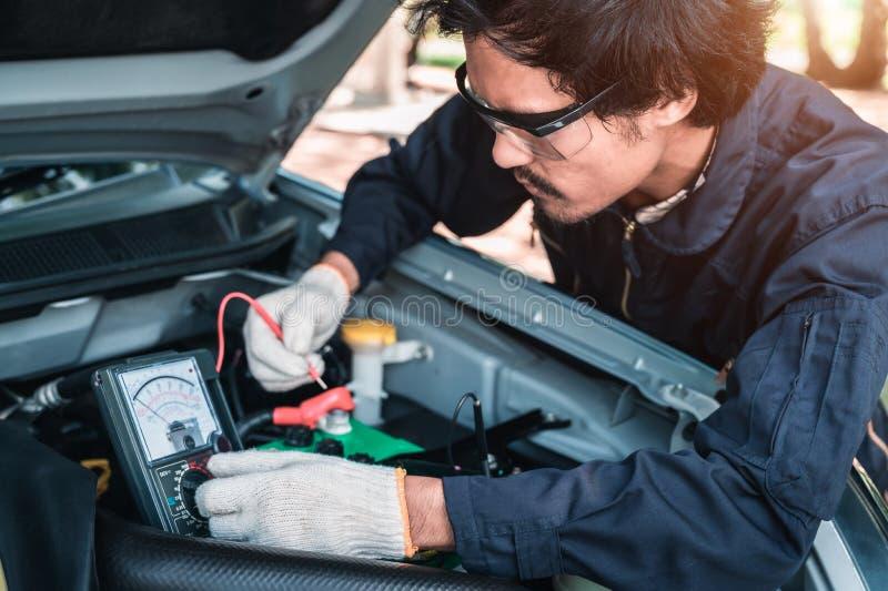 Il fuoco selettivo un meccanico utilizza un voltometro del multimetro per controllare il livello di tensione in un accumulatore p immagini stock