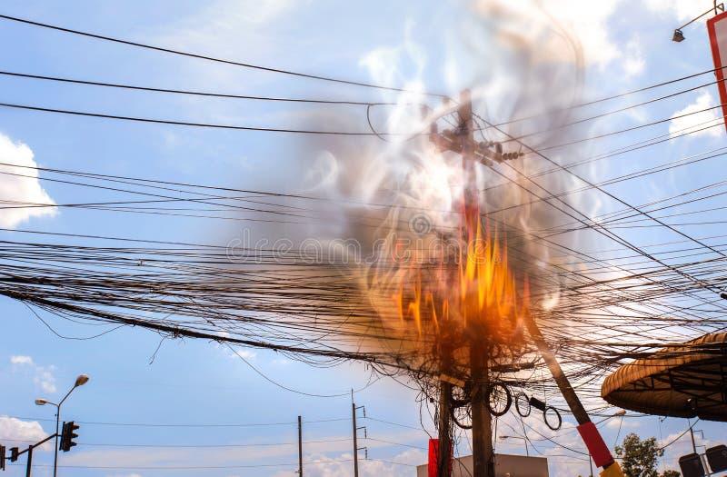 Il fuoco sta bruciando al potere dei cavi di alta tensione, energia elettrica del cavo di groviglio del cavo del pericolo fotografia stock