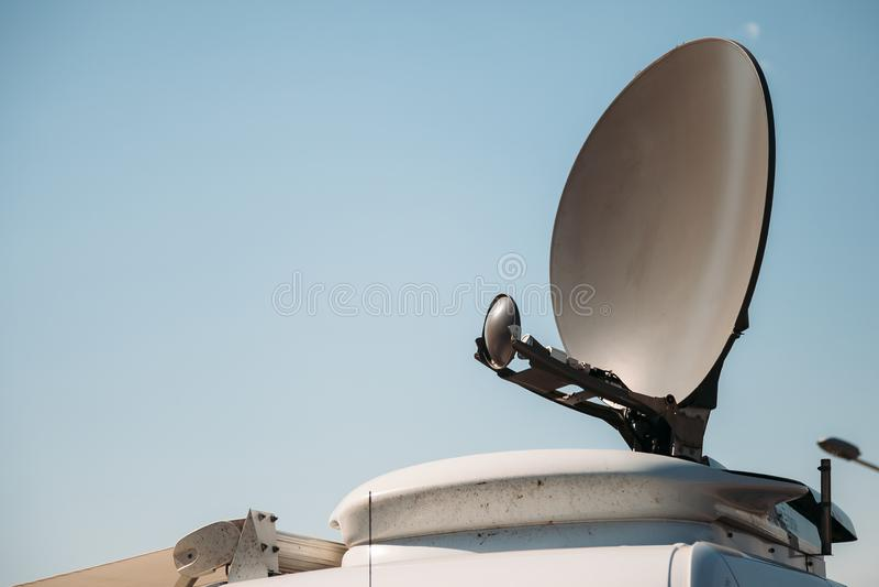 Il furgone satellite parcheggiato dell'automobile TV trasmette gli eventi di ultime notizie ai satelliti orbitanti fotografia stock