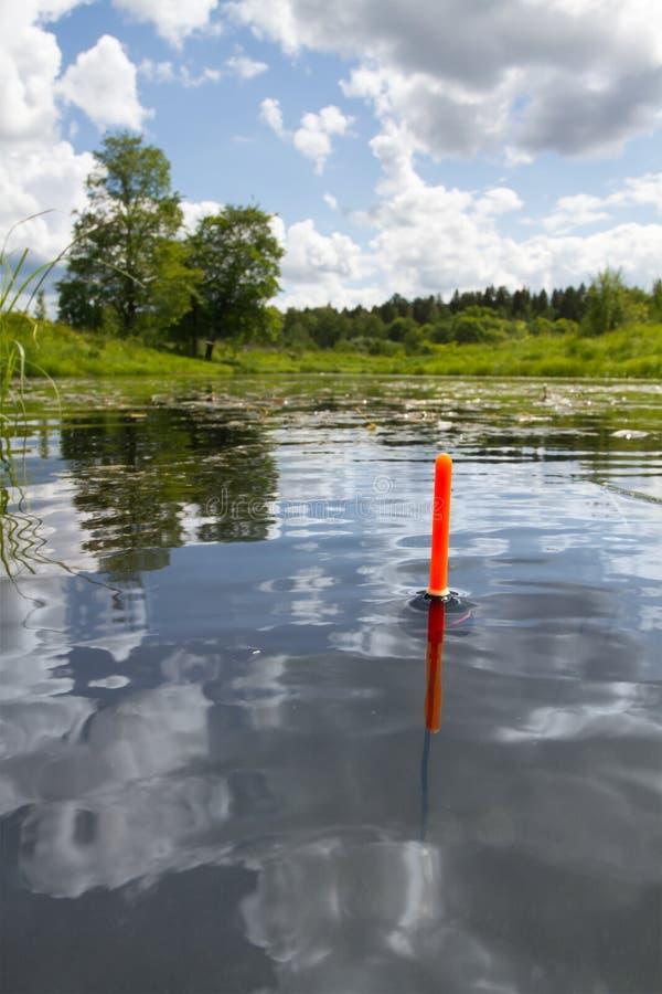 Il galleggiante da pesca si siede verticalmente nell'acqua di un lago calmo immagini stock