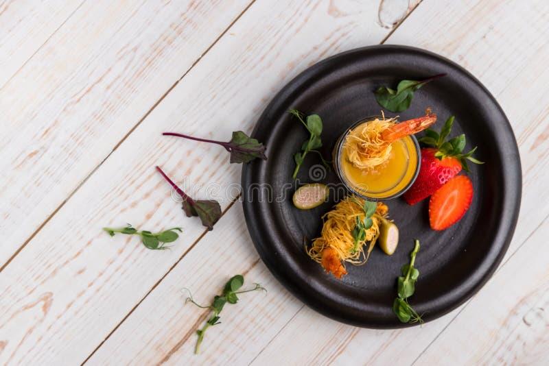 Il gamberetto croccante in crosta di Kataifi ed il timo con Champagne Sauce in vetri e fragole si trovano su una banda nera su un fotografia stock