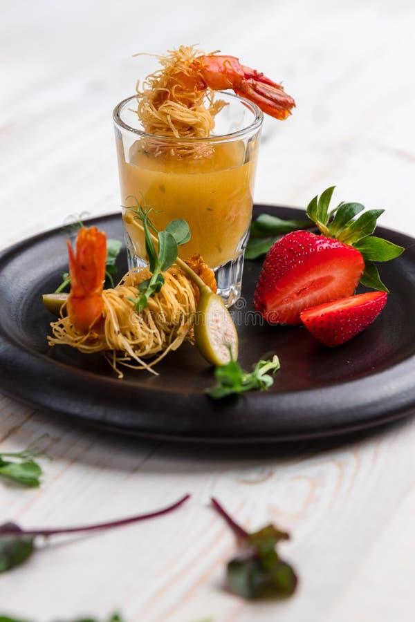 Il gamberetto croccante in crosta di Kataifi ed il timo con Champagne Sauce in vetri e fragole si trovano su una banda nera su un fotografie stock