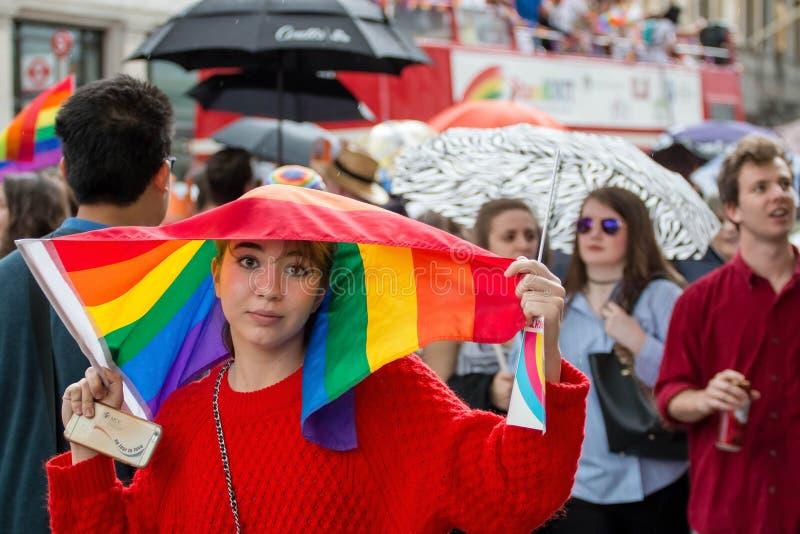 Il gay Pride Parade, donna di LGBT utilizza la bandiera dell'arcobaleno per riparare da pioggia immagini stock libere da diritti