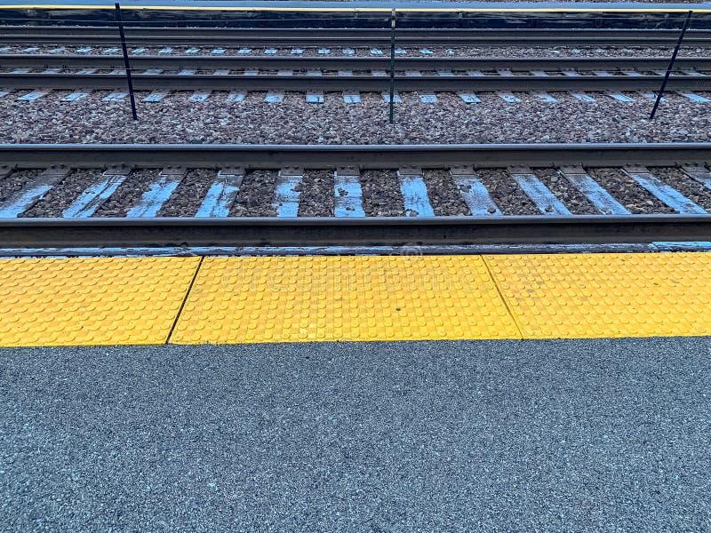 Il gelo si sistema sui binari ferroviari lungo il binario della stazione immagini stock