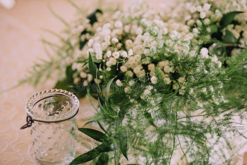 Il gelsomino bianco dei fiori si inverdisce il vaso di vetro del mazzo dell'asparago fotografie stock
