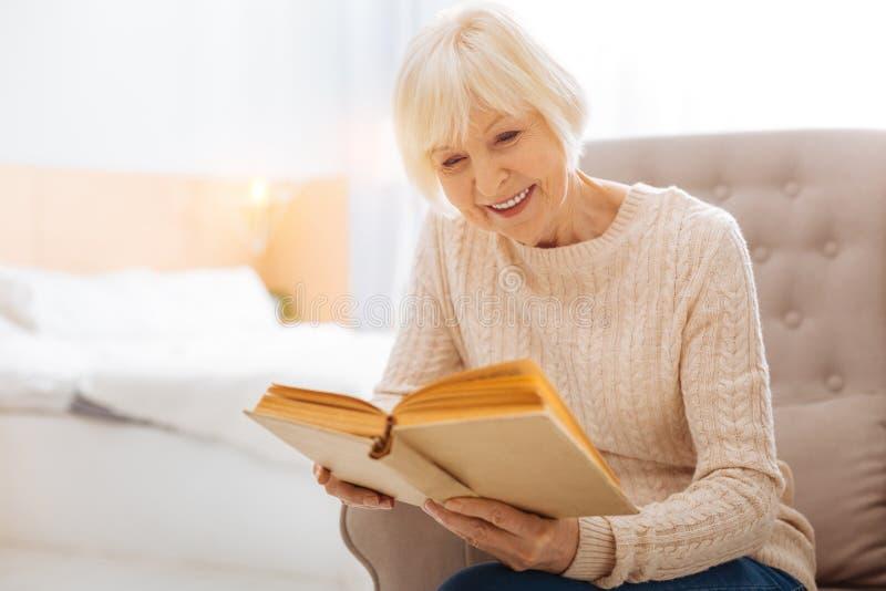 Il genere piacevole ha invecchiato la donna che sorride e che legge un libro adorabile fotografia stock