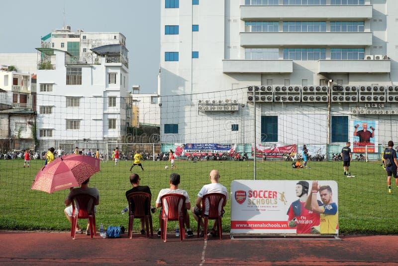 Il genitore sta aspettando il loro gioco del bambino footbal immagini stock libere da diritti