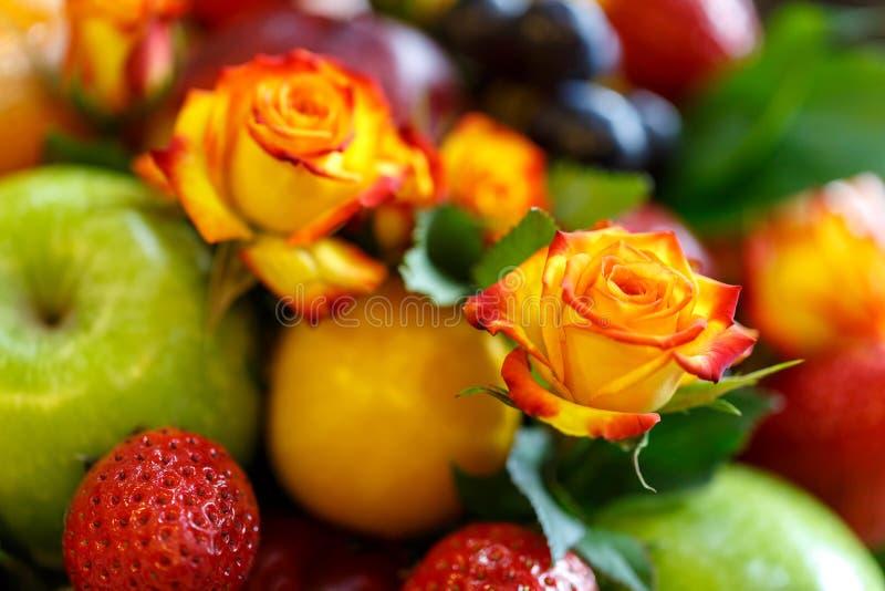 Il germoglio di un rosso arancio è aumentato contro un fondo di un mazzo luminoso della frutta fotografia stock