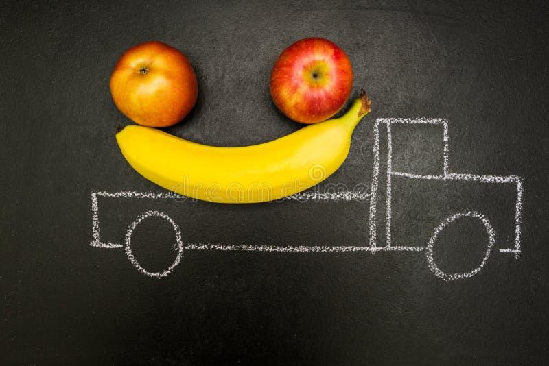 Il gesso ha dipinto il camion caricato con le banane e le mele su un fondo nero immagine stock