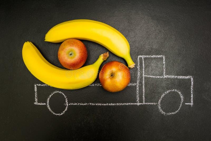 Il gesso ha dipinto il camion caricato con le banane e le mele su un fondo nero fotografia stock