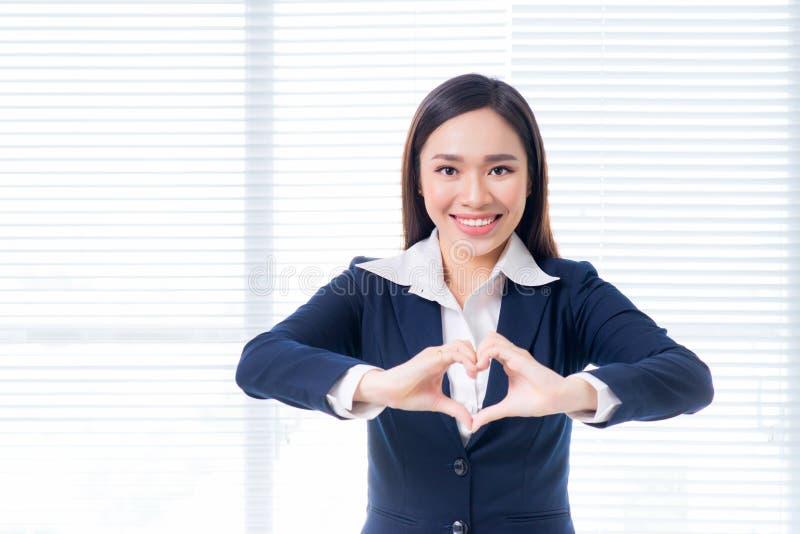 Il gesto asiatico sicuro della donna di affari passa la fabbricazione della forma del cuore immagine stock libera da diritti