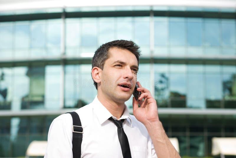 Il gestore parla sul telefono attraverso l'ufficio fotografia stock