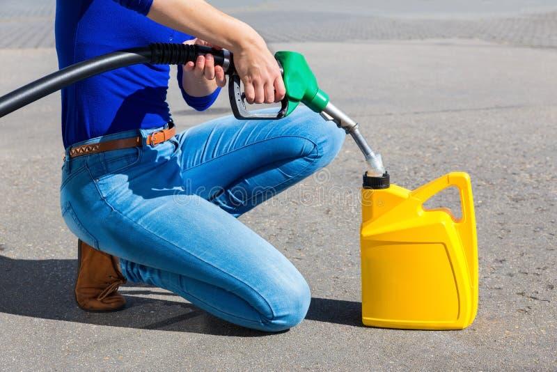Il giallo di riempimento della donna può con benzina o benzina fotografia stock libera da diritti