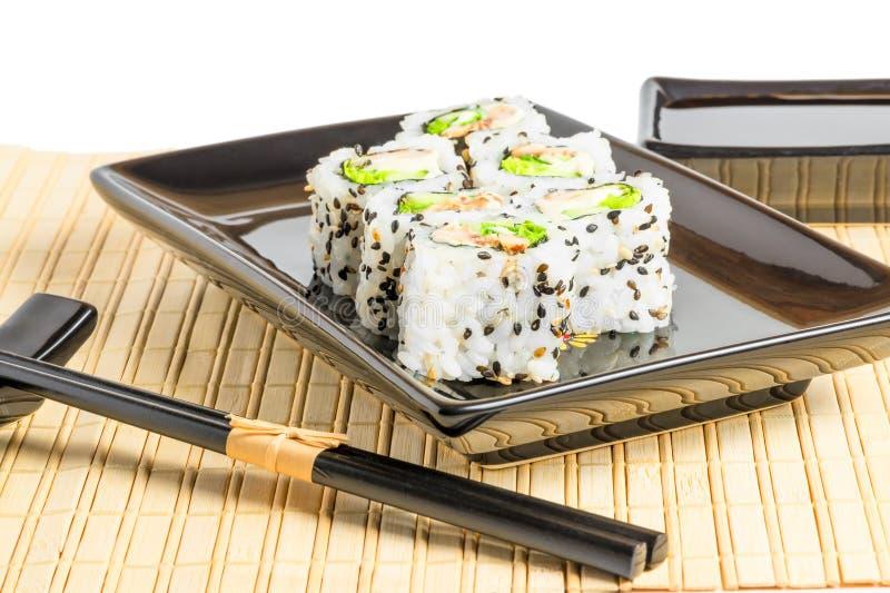 Il giapponese bianco rotola sull'i piatti neri immagini stock
