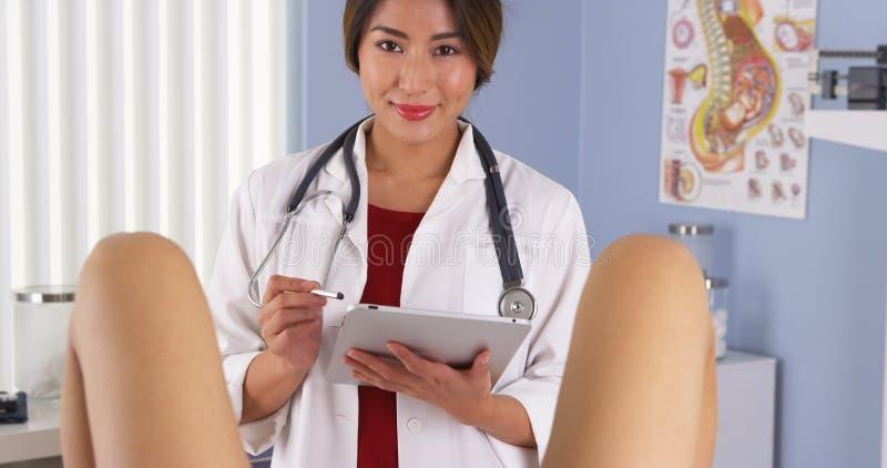 Il ginecologo giapponese esamina il paziente nella stanza dell'esame dell'ospedale immagini stock