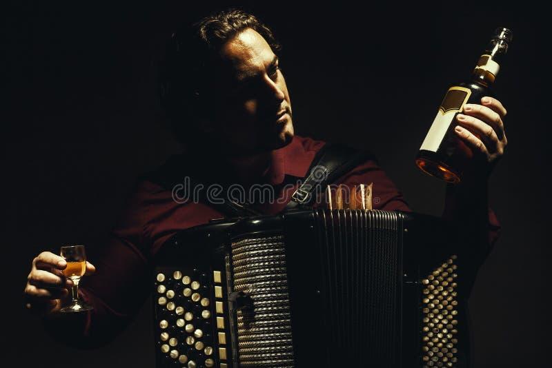 Il giocatore cromatico della fisarmonica con una bevanda di spirito fotografia stock