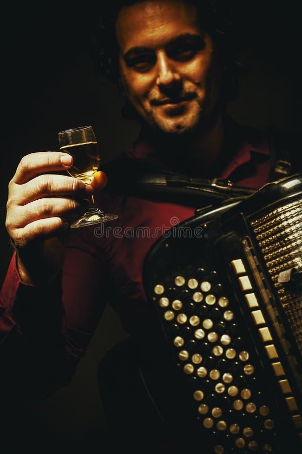 Il giocatore cromatico della fisarmonica e un vetro della bevanda alcolica immagini stock libere da diritti