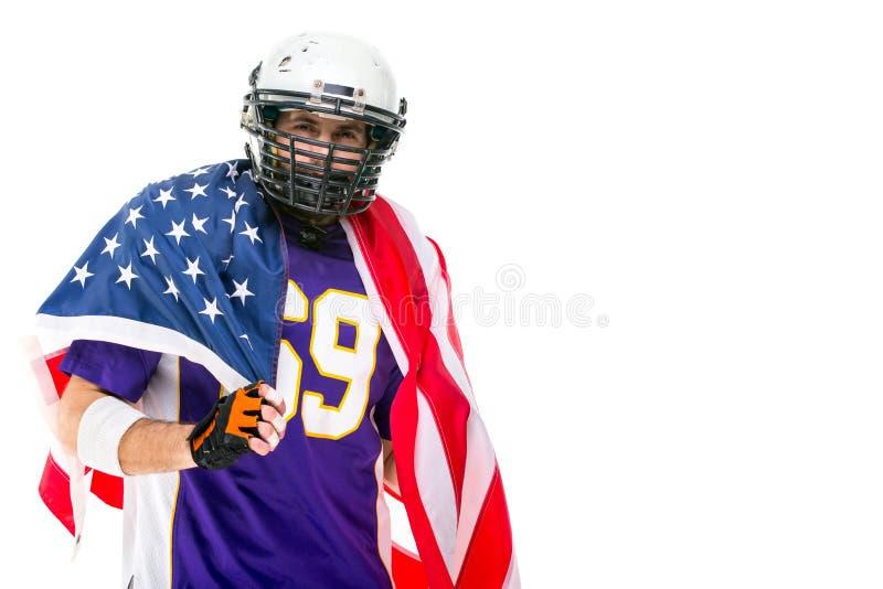 Il giocatore di football americano celebra la conquista con la bandiera americana immagini stock libere da diritti