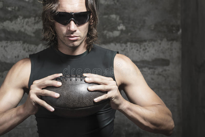 Il giocatore di football americano sta tenendo la palla in mani immagini stock