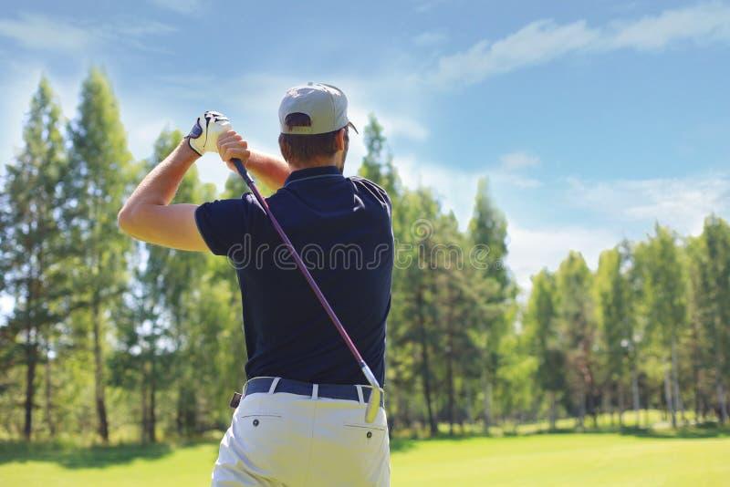 Il giocatore di golf colpisce un tratto navigabile sparato verso la casa del club fotografia stock libera da diritti