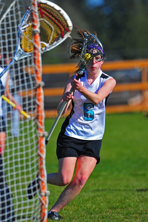 Il giocatore di Lacrosse delle ragazze si muove dentro per un colpo fotografia stock