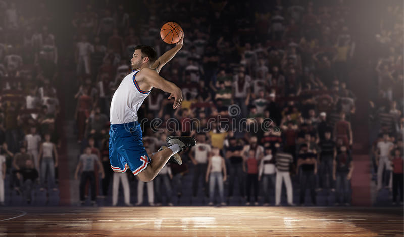 Il giocatore di pallacanestro che salta con la palla sullo stadio fotografia stock