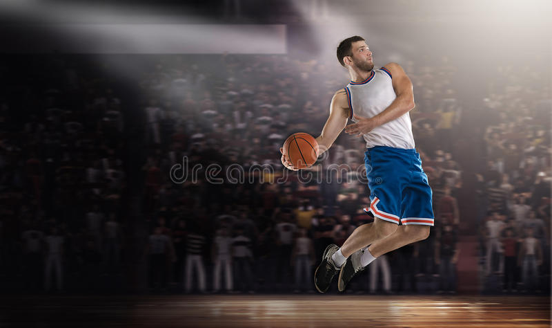 Il giocatore di pallacanestro che salta con la palla sullo stadio alle luci immagini stock