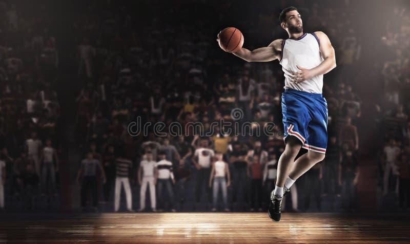 Il giocatore di pallacanestro che salta con la palla sullo stadio alle luci fotografia stock