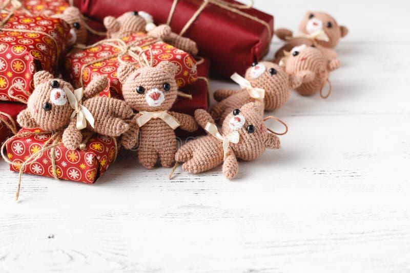 Il giocattolo ha tricottato l'orso con la scatola del gigt sulla tavola fotografie stock libere da diritti