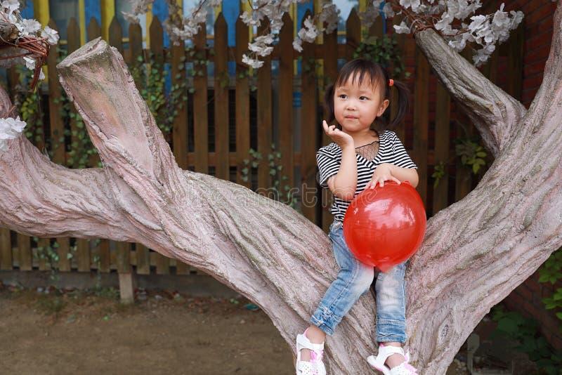 Il gioco adorabile adorabile impertinente sveglio della bambina con il pallone e si siede da un albero si diverte all'aperto nel  fotografia stock libera da diritti