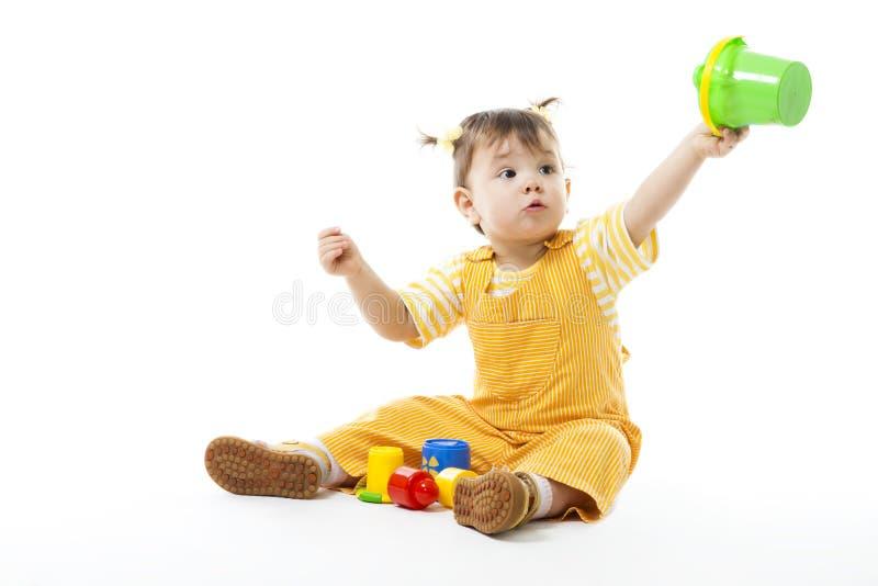 Il gioco del bambino si siede e con i giocattoli, tenenti il secchio immagine stock libera da diritti