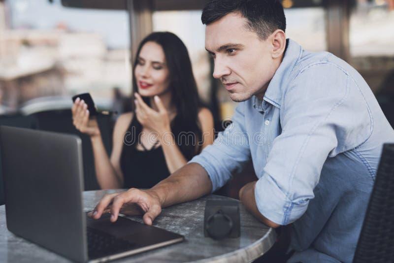 Il giornalista esamina il computer portatile mentre la ragazza guarda nello specchio fotografia stock