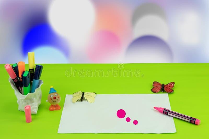 Il giorno dei bambini felici Il posto di lavoro dal bambino sta dipingendo sua madre un'immagine ed alcuni giocattoli sopra il fo fotografie stock libere da diritti