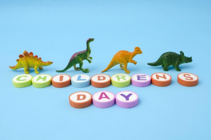 Il giorno dei bambini ha fatto dalle lettere variopinte e dai giocattoli di plastica del dinosauro fotografia stock libera da diritti