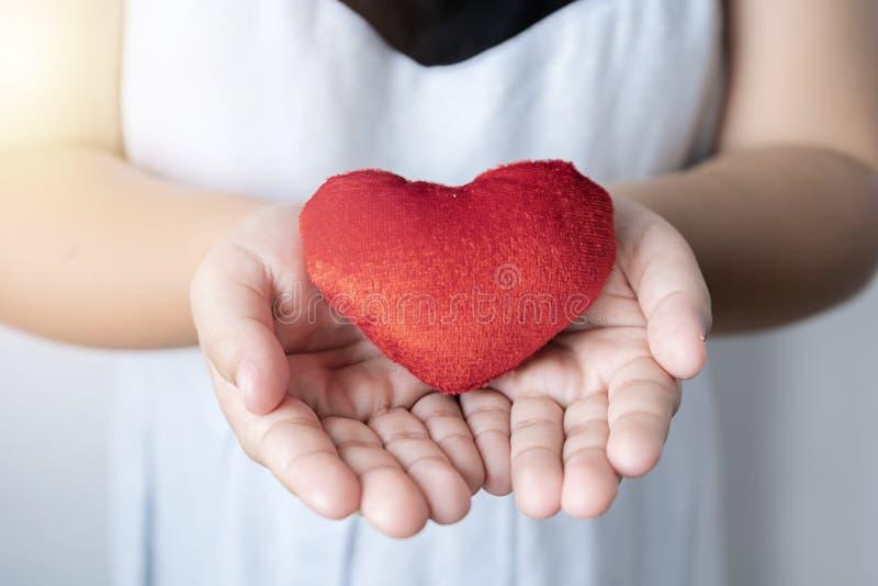 Il giorno di biglietti di S. Valentino, il cuore rosso è disposto sulla mano della ragazza immagine stock libera da diritti