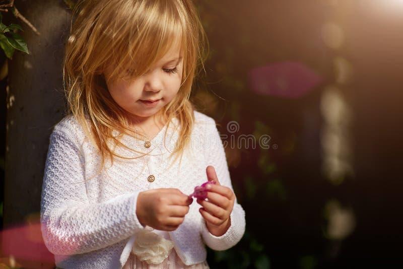 Il giorno soleggiato, la bambina si trova sull'erba fotografie stock libere da diritti