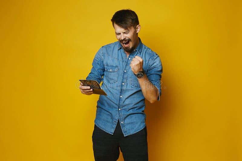 Il giovane è felice di ottenere un visto in passaporto, pantaloni a vita bassa alla moda con la barba e baffi in camicia alla mod fotografia stock libera da diritti