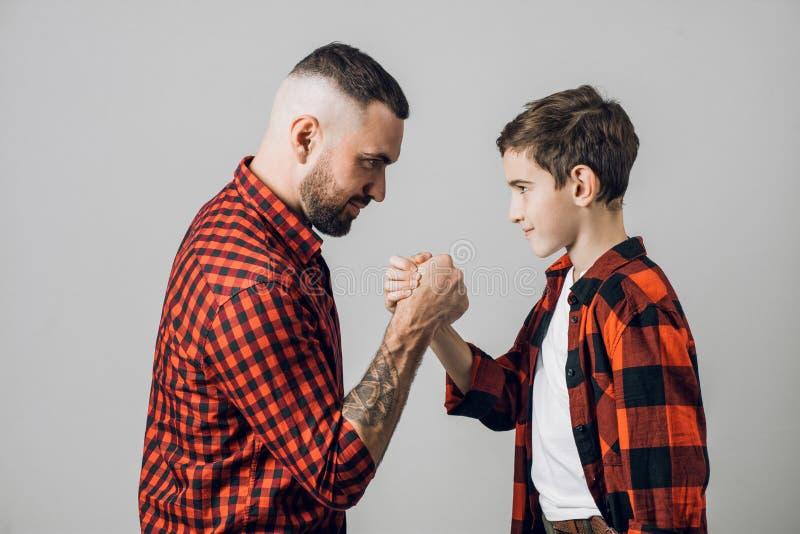 Il giovane è fiero di suo figlio il papà contribuisce a suo figlio a superare i problemi fotografie stock libere da diritti