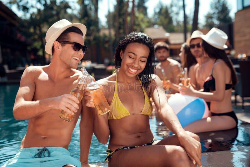 Il giovane è occhiali da sole e donna allegra che incoraggiano con le bottiglie di birra nella piscina fotografie stock libere da diritti