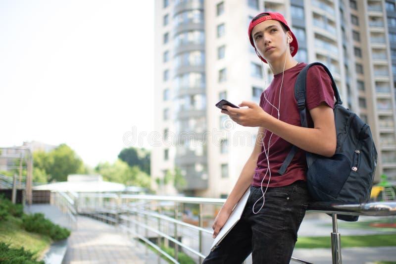 Il giovane è in piedi con uno zaino e tiene in mano uno smartphone in città Un adolescente usa il cellulare, all'aperto caucasico fotografia stock