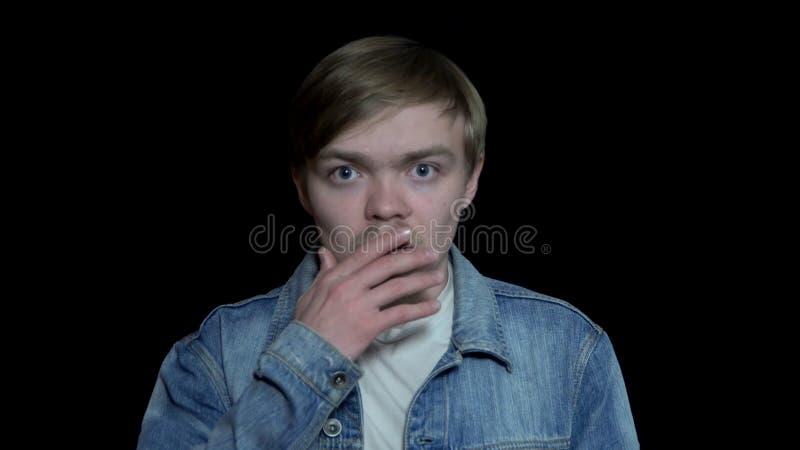 Il giovane è sorpreso e chiude la bocca con la palma Uomo colpito da che avvenimento Espressioni facciali ed emozioni umane fotografie stock libere da diritti