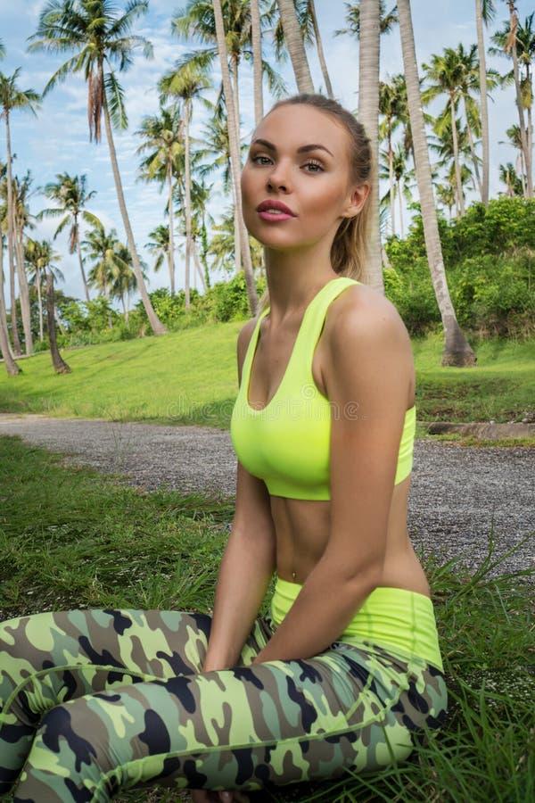 Il giovane abbigliamento d'uso femminile felice biondo grazioso di esercizio che si siede sull'erba nelle palme tropicali fa il g fotografia stock libera da diritti