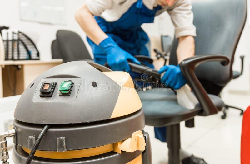 Il giovane in abiti da lavoro ed in guanti di gomma pulisce la sedia dell'ufficio con attrezzatura professionale fotografia stock